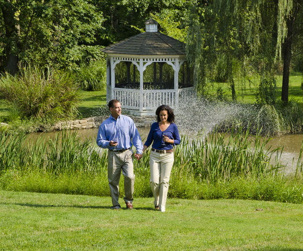 A man and woman walk on the grass holding hands.
