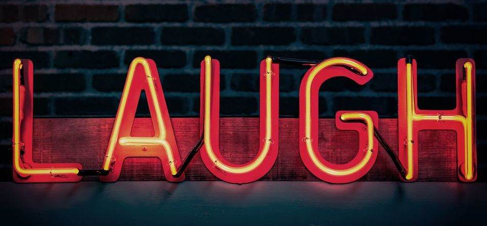 A Neon Laugh Sign In Front of Brick Wall