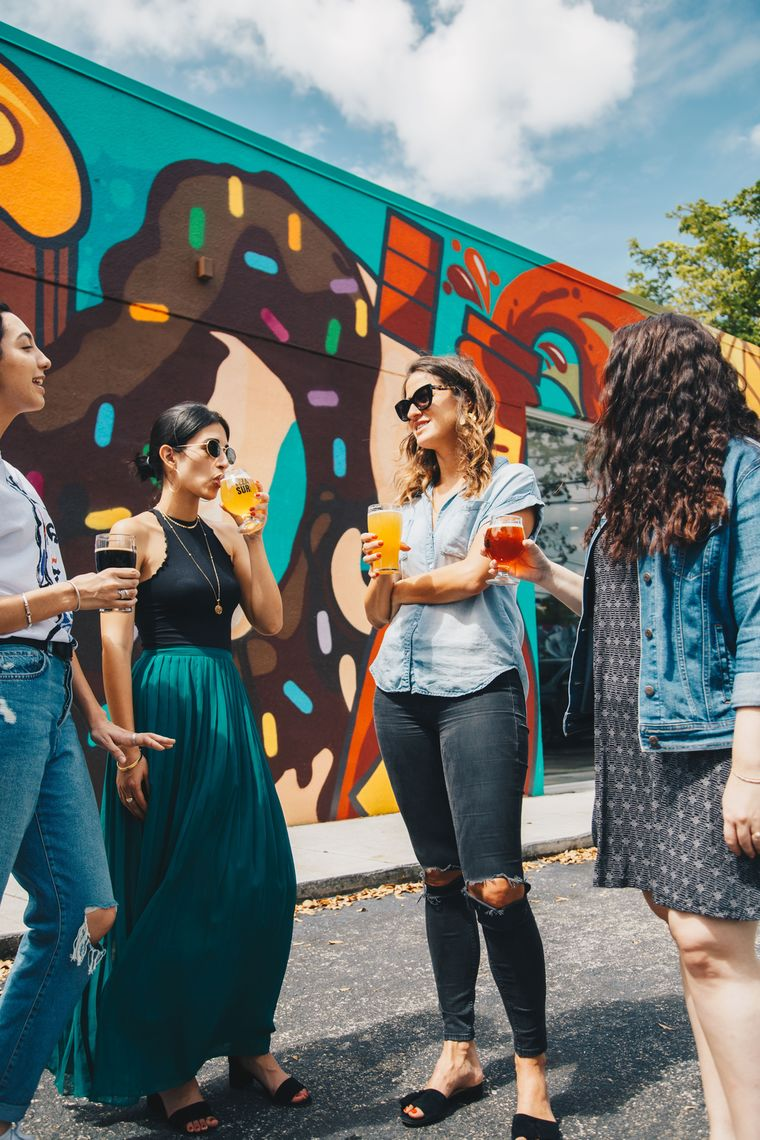 Picture of four women in front of street art drinking beer