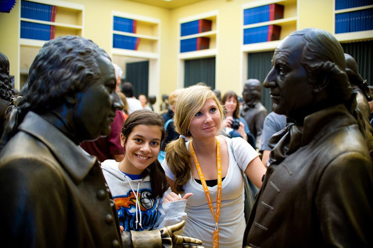 Two Young Women Stand in Front of Statue at Constitution Center