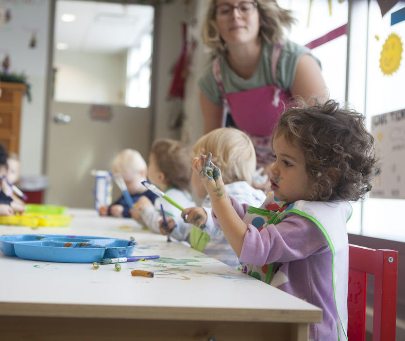 Toddlers paint while their teachers watch them